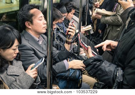 Tokyo - March 2, 2015: People Busy With Smartphones And Tablets In The Underground Train