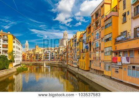 Colorful yellow and orange houses and bridge Pont de Sant Agusti reflected in water river Onyar, in Girona, Catalonia, Spain. Church of Sant Feliu and Saint Mary Cathedral at background. poster