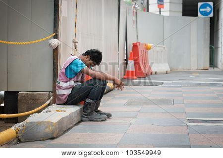 Exhausted Construction Worker Takes A Break In Singapore