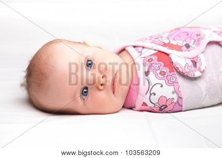 Three month baby girl wrapped in a modern winged baby swaddle laying on a bed