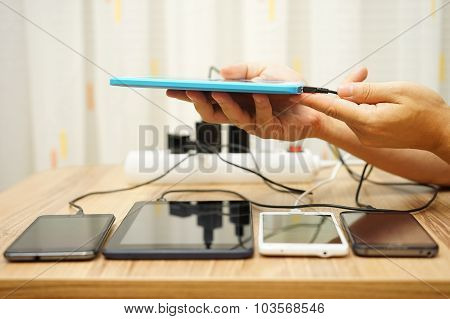 Men Connected Charger To Tablet Computer After Four Digital Devices Already Charging