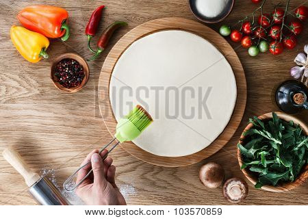 Spreading Tomato Sauce On A Pizza Base