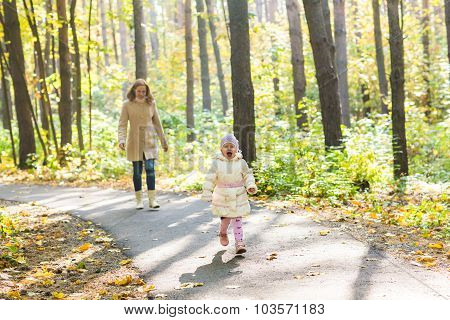 Mother and daughter walking in the autumn park