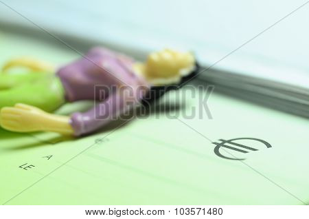 Figurine Woman Lying On A Checkbook With Euro Symbol