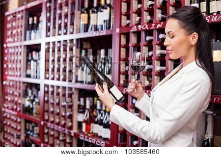 Cheerful young female vintner is tasting alcohol drink