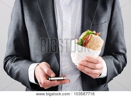 Busy on the go business man in suit texting with smartphone in one hand and holding his BLT ciabatta roll in the other