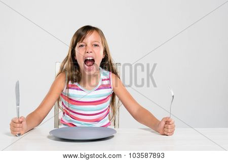 Hungry angry young girl screaming, shouting, throws a tantrum sitting at a table with empty plate