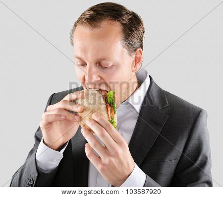 Busy hardworking business man eats lunch at his desk while working