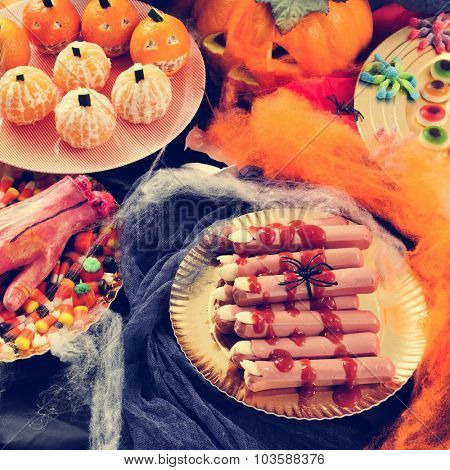 some plates with different Halloween food, such as candies, scary fingers or mandarines as pumpkins, with different scary ornaments as an amputated hand, spiders and cobwebs