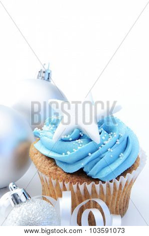 Festive holiday cool tone blue winter cupcakes with large star and sliver christmas decorations