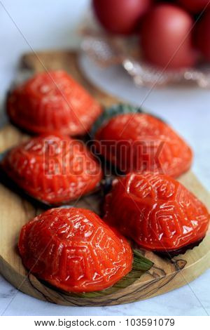 Ang ku kueh or chinese red tortoise cake is traditionally eaten together with dyed red eggs and mandarin oranges to celebrate the first month of a baby's birth poster