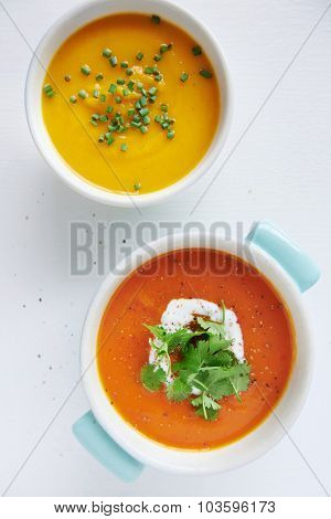 Roasted butternut pumpkin squash soup and a tomato sweet potato soup garnished with coriander and coconut milk cream