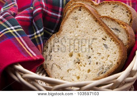 Sliced breads in a woven basket lined with a checked red cloth.