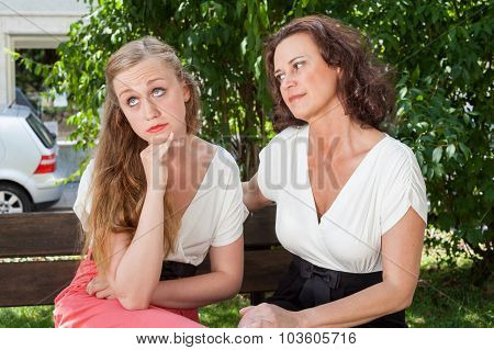 Two Women Having Argument On Park Bench