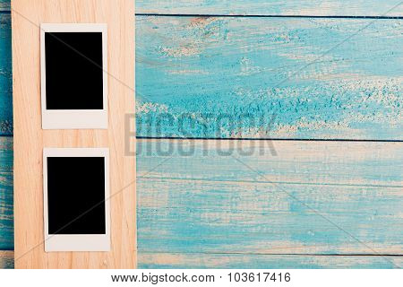 Blank instant photo frames on wooden background.