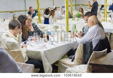 People Having Dinner In The Sukkah