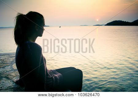Young Woman Sitting On The Beach At Sunset, A Symbol Of Dreams And Longing