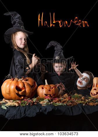 Halloween. Two little witches, skull surrounded by pumpkins, spiders and foliage
