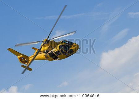Yellow Helicopter Flight In Cloudy Sky