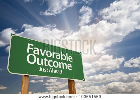 Favorable Outcome Green Road Sign With Dramatic Clouds and Sky.