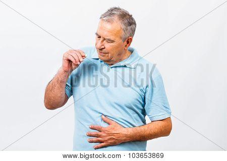 Senior man taking pills for stomachache