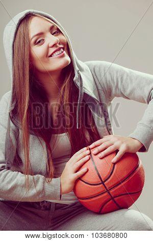 Happy sporty teenager girl wearing hooded sweatshirt holding basketball. Teen sport. poster
