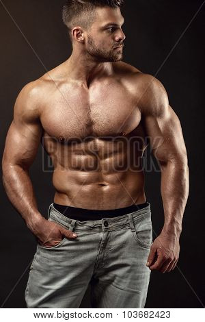 Strong Athletic Man Fitness Model Torso showing big muscles over black background poster