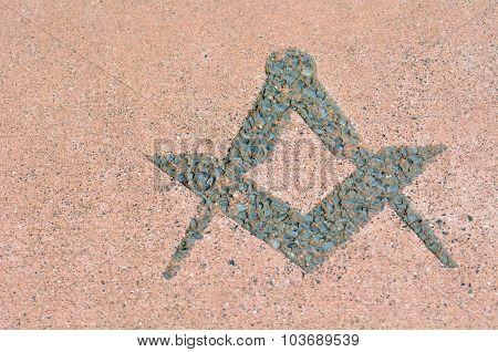 Freemasonry symbol made from stones on the ground.