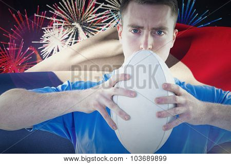 Rugby player holding a rugby ball against fireworks exploding over football stadium poster