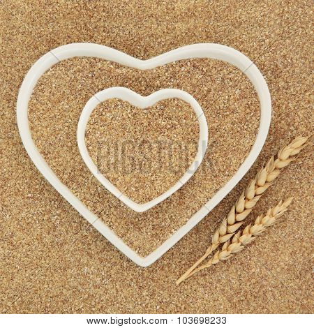 Wheatgerm in heart shaped white porcelain dishes with wheat sheaths forming an abstract background.