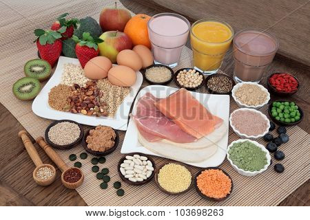 Health and body building food with fish and meat, supplement powders, vitamin tablets, pulses, nuts, vegetables, fruit and high protein and juice smoothie shakes.