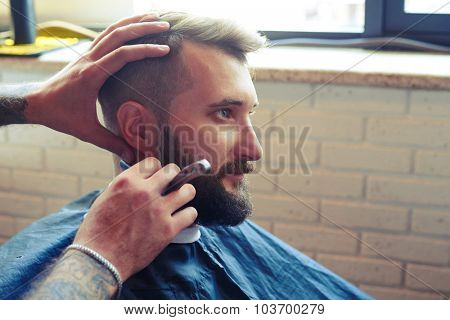 portrait of handsome man in barbershop. barber shaving man with straight razor