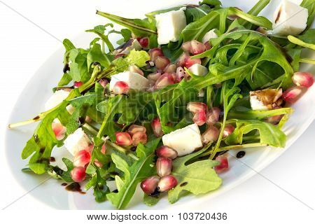 Arugula Salad With Feta Cheese And Pomegranate On A White Plate