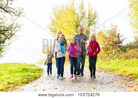 Girls going ahead at family walk through the park in fall or autumn