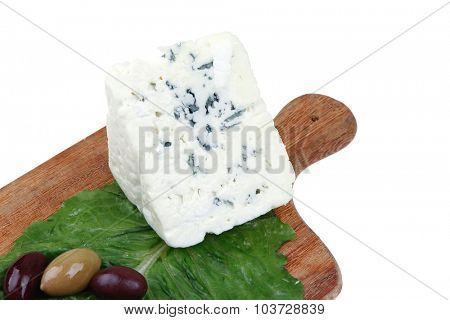 stilton cheese on wooden platter with olives and tomato isolated over white background