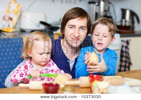 Father With Two Kids At Kitchen