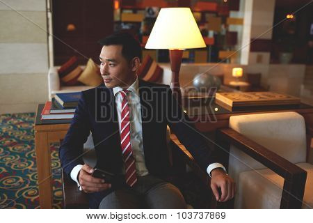 Confident rich men entrepreneur waiting for a call on his cell telephone during work break