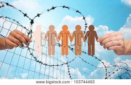 crime, imprisonment, refugee and humanity concept - multiracial couple hands holding chain of paper people pictogram over blue sky and barb wire background