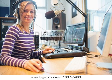 Portrait of female radio host using computer while broadcasting in studio