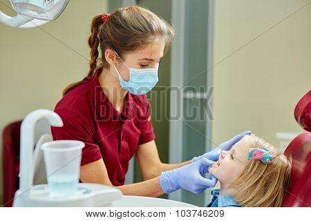 Pediatric dentist examining little girls teeth in the dentists chair