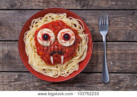 Halloween scary pasta food vampire face with big eyes and moustaches in red dish for celebration par