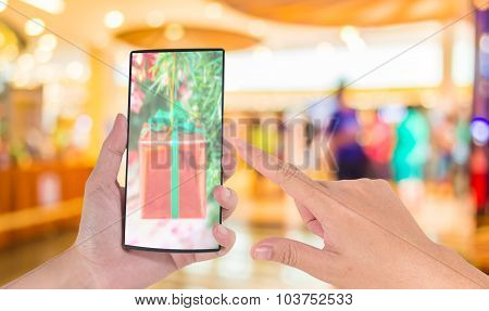 Male Hand Is Holding A Modern Touch Screen Phone And Blurred Image Of Shopping Mall .