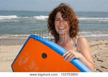 Woman  Having Fun Bodyboarding Under Sun And Blue Sky