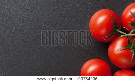 red tomatoes on black. Top view. Header for website