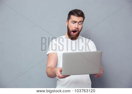 Portrait of a man with stupid mug using laptop over gray background