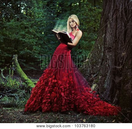 Beautiful blonde reading a book in a forest