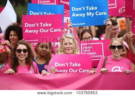Pink clad activists with signs
