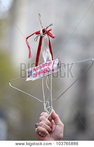 Stylized coat hanger held aloft