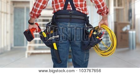 Electrician man with drill and wire cable over construction background.