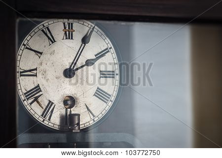 old retro clock with roman numerals behind glass